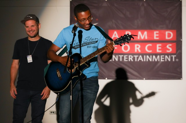 U.S. Army Spc. Takeem Myers, a financial management technician with the 374th Financial Management Support Unit, shows off his guitar talents after comedian Johnny Cardinale invited him on stage at Camp Bondsteel, Kosovo, Aug. 5, 2019. Myers thanked the comedians for coming out and enjoyed interacting with the comedians after the show. (U.S. Army photo by Spc. Grant Ligon, 40th Public Affairs Detachment)
