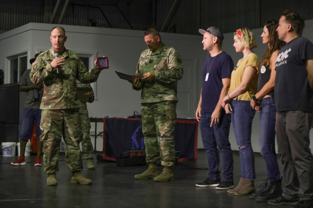 Multinational Battle Group - East Commander, Col. Robert Hughes (left) presents Armed Forces Entertainment comedians with command coins for their World Wide Comedy tour show at Camp Bondsteel, Kosovo, Aug. 5, 2019. Command Sgt. Maj. Scott Mechkowski (center-right) presented the comedians with certificates of appreciation. (U.S. Army photo by Spc. Grant Ligon, 40th Public Affairs Detachment)