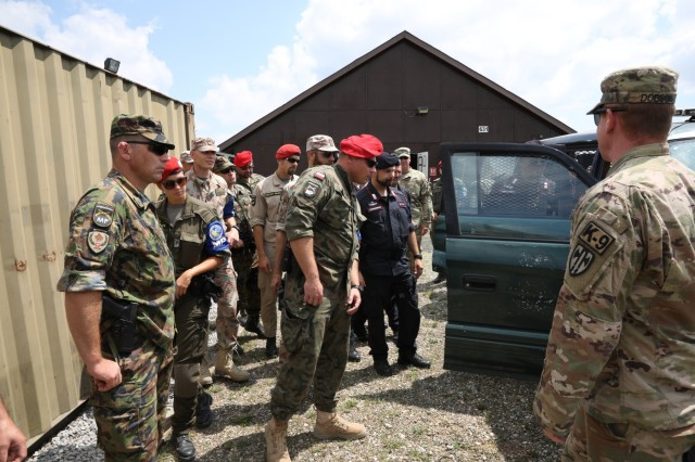 NATO KFOR 26 rotation's Military Police members from Multinational Battle Group East and West, the International Military Police and the Multinational Specialized Unit examine a vehicle for notional explosives on Camp Bondsteel July 25, 2019. The examination followed a MNBG-E Task Force MP K-9 handler's demonstration. The various MP units came together for a monthly meeting intended to disseminate information and build camaraderie. (U.S. Army Photo by Spc. Lynnwood Thomas, 40th Public Affairs Detachment)
