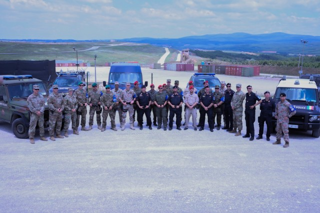 Military Police members of KFOR 26's Multinational Battle Group East and West, the International Military Police and the Multinational Specialized Unit stand together after a K-9 demonstration on Camp Bondsteel, July 25, 2019. The MP units came together for a monthly meeting intended to disseminate information and build camaraderie. (U.S. Army Photo by Spc. Lynnwood Thomas, 40th Public Affairs Detachment)