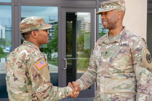 A staff sergeant greets a specialist. The Army is now requiring that Soldiers be assigned a sponsor before any move.