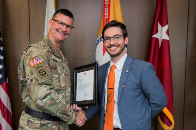 Kyle Crawford receives a two-star note from Maj. Gen. Jeffrey Drushal, commander of the Security Assistance Command, at the July town hall.