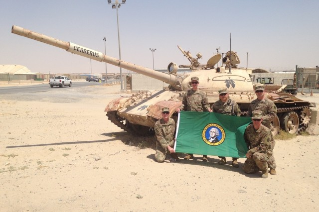 "Members of the 122D Public Affairs Operations Center pose in front of a disabled tank named ""Cerbrus""  at Camp Arifjan, Kuwait. Arifjan is known as ""The Gateway"" because soldiers heading into theater must first check-in through Kuwait. From left to right: Master Sgt. Neal Mitchell, Capt. James Deakins, Col. Stanley Seo, Capt. Benjamin Burbank and Maj. Eric Trovillo."