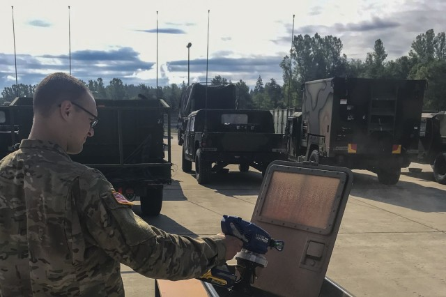 Army Sgt. Richard Dial of the US Army European Command Chemical Biological Radiological Nuclear Explosive Detachment in Grafenwoehr, Germany applies sprayable decontaminant slurry to a scaled-down Humvee door.