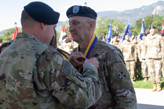 Chief Warrant Officer 5 Jimmie Brooks, the 4th Combat Aviation Brigade, 4th Infantry Division's outgoing command chief warrant officer, is awarded a Legion of Merit from Col. Scott Gallaway, left, outgoing commander, 4th Combat Aviation Brigade, 4th Infantry Division, during a change-of-command ceremony on Founders Field, Fort Carson, Colorado, July 26, 2019. The Legion of Merit is a military award given for exceptionally meritorious conduct in the performance of outstanding services and achievements.(U.S. Army photo by Sgt. Daphney Black)