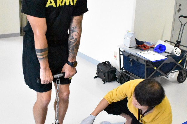 Staff Sgt. Josh Beysselance, left, assigned to the 78th Signal Battalion, tests his back strength during a fitness test at the Yano Fitness Center at Camp Zama, Japan, Aug. 14. Shannon Vo, a health educator at the Camp Zama Army Wellness Center, reads the results.