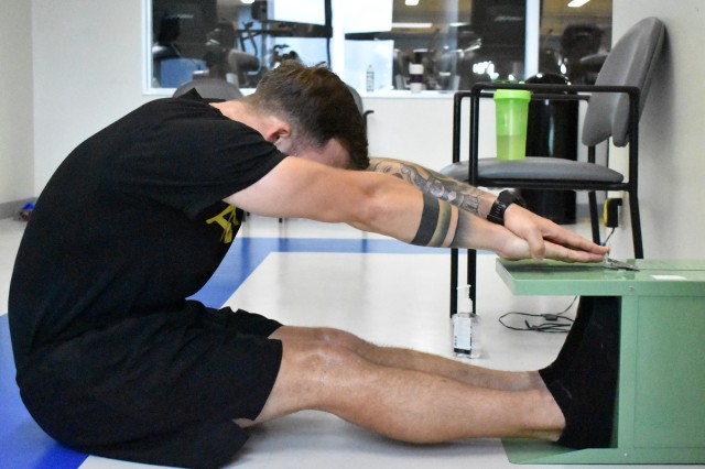 Staff Sgt. Josh Beysselance, left, assigned to the 78th Signal Battalion, tests his flexibility during a fitness test at the Yano Fitness Center at Camp Zama, Japan, Aug. 14.