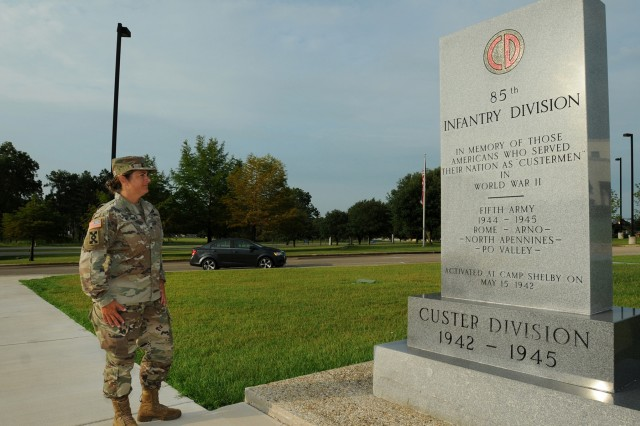 Brig. Gen. Kris A. Belanger, Commanding General, 85th U.S. Army Support Command, reflects on the command's lineage while looking at a monument at Camp Shelby, Mississippi, honoring the World War II Soldiers of the, then, 85th Infantry Division which fought overseas during World War II. Four Soldiers from the 85th Infantry Division received the Medal of Honor for their service in action. Two of them received the medal posthumously. Belanger visited Camp Shelby from August 8th through 11th to observe her observer coach/trainers conduct training lanes for Infantry Soldiers from the Florida National Guard during eXportable Combat Training Capability 19-05. (U.S. Army Reserve photo by Sgt. David Lietz)