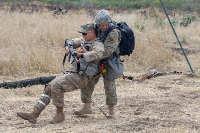 Col.  Fernando Güereña , chief medical officer from Madigan Army Medical Center, evacuates a casualty on the fifth day of testing on a combat testing lane during the Expert Field Medical Badge competition at Joint Base Lewis McChord, Washington, Aug. 12.