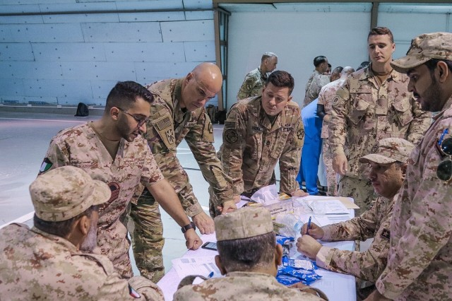 Soldiers discuss training during a basic field emergency care workshop led by the United States Military Hospital - Kuwait at the Kuwait North Military Medical Complex, July 31, 2019. (U.S. Army Reserve photo by Spc. Hector Mejia)