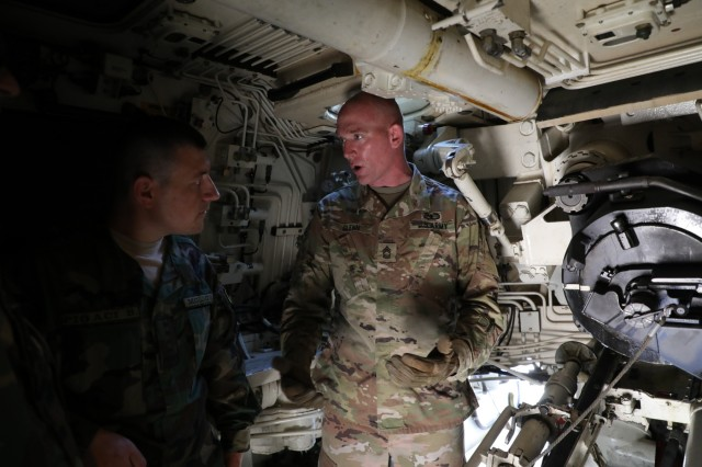 North Carolina National Guard Master Sgt. Kevin Glenn, a 139th Regional Training Institute instructor, explains firing procedures for an M109A6 Paladin to Moldovan National Army Capt. Boris Pigaci, a field artillery officer, during a visit to the 139th RTI at Fort Bragg on Aug. 12, 2019.  The North Carolina National Guard has partnered with Moldova for over 20 years as part of the State Partnership Program, which is created to foster military and civil sector bonds between former Soviet Union countries while conducting military-to-military and civilian-to-military activities to maintain international defensive security and to increase peace and stability across Europe.