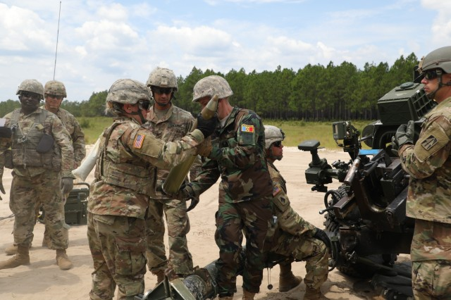 U.S. Army Sgt. Whitney Belwood (left), a field artillery section chief student at the 139th Regional Training Institute, hands Moldovan National Army Lt. Victor Suceanu, a field artillery officer, an M105 round for a M119A3 Howitzer during a visit to the 139th RTI at Fort Bragg on Aug. 12, 2019.  The North Carolina National Guard has partnered with Moldova for over 20 years as part of the State Partnership Program, which is created to foster military and civil sector bonds between former Soviet Union countries while conducting military-to-military and civilian-to-military activities to maintain international defensive security and to increase peace and stability across Europe.