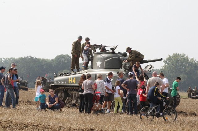 "People view the tank in Mesvin, a village near Mons, Belgium, during Tanks in Town in 2014. The annual event is held in Mons to commemorate the liberation of the city in 1944 by the 83rd Reconnaissance Battalion of the 3rd U.S. Armored Division ""Spearhead."""
