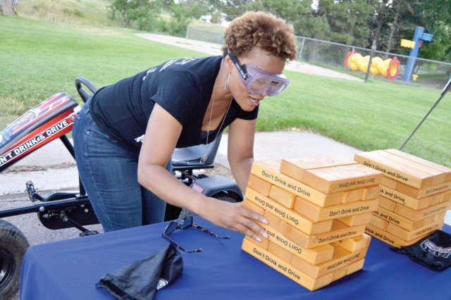 "FORT CARSON, Colo. - Bonita Spears, U.S. Army Garrison Fort Carson, sexual assault response coordinator, dons ""drunk"" goggles and attempts to move ""Giant Jenga"" pieces at the Army Substance Abuse Program information booth Aug. 6, 2019, during the National Night Out event on post. (Photo by Scott Prater)"