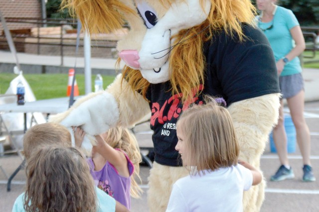 FORT CARSON, Colo. - Daren the Lion, the Drug Abuse Resistance Education program's official mascot, greets Family members Aug. 6, 2019, during the National Night Out event at Soldiers' Memorial Chapel. (Photo by Scott Prater)