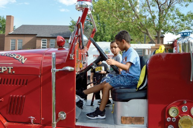 FORT CARSON, Colo. - Noah Crockham, 6, tests the brake pedal operation in the driver's compartment of a 1942 Seagrave Fire Engine, while his brother Eli Crockham, 4, judges the seat comfort during Fort Carson's National Night Out event Aug. 6, 2019. (Photo by Scott Prater)