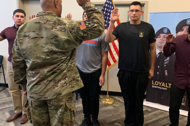 Luis Enrique Pinto Jr., second from the right, takes the Oath of Enlistment after he lost 113 pounds in seven months in order to pass the Army's weight requirements. Luis enlisted as a 14E, which is responsible for operating and maintaining Patriot weapon systems, and plans to report to basic training in September.