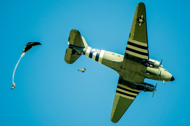Two members of the Liberty Jump Team, a commemorative team of volunteer parachutists, jump out of a restored C-47 Skytrain. The Maneuver Center of Excellence and Fort Benning commemorated the 2019 National Airborne Day Aug. 16 at Fryar Drop Zone at Fort Benning. National Airborne Day is the anniversary of the first paratrooper test jump, which took place at Fort Benning 79 years ago. The U.S. Army Parachute Team from Fort Bragg, N.C., the Silver Wings jump team from Fort Benning and the volunteer Liberty Jump Team performed parachute jumps to honor the history of U.S. Army airborne Soldiers.