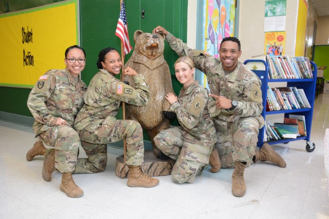 Masters of Social Work students 2LT Marcela Mcduffie, LT Camethia Russell-Morris, 2LT Jamie Webb, and 2LT Jaron Stubbs pose in front of the Briscoe Elementary school bear mascot, donated by the 187th MED BN to the school in 2016.