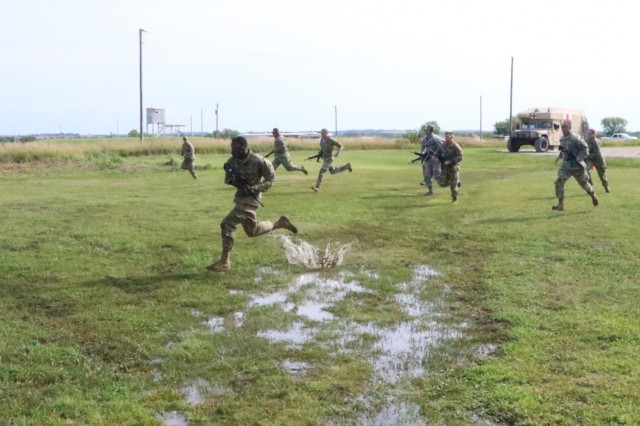 Two teams race each other across muddy terrain to the firing line to knock down metal targets from 200 meters away on the last day of the annual Adjutant General's Marksmanship Competition in Salina, Kansas, Aug. 11.