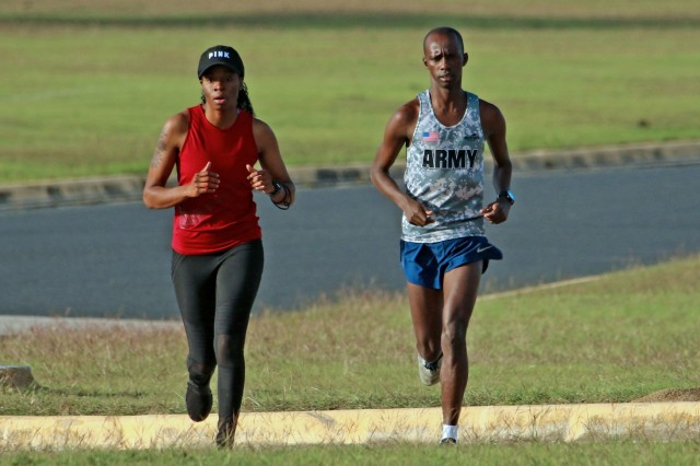 Sgt. Michael K. Biwott (right), a supply sergeant with 2nd Squadron, 3rd Cavalry Regiment, and Sgt. Shannera Anderson, a supply specialist and Biwott's supervisor, run together at Long Branch Park in Killeen, Texas, Oct. 25, 2018.  Biwott runs at least 60 miles a week in order to achieve his American dream of running track or cross country in the U.S. Olympics.