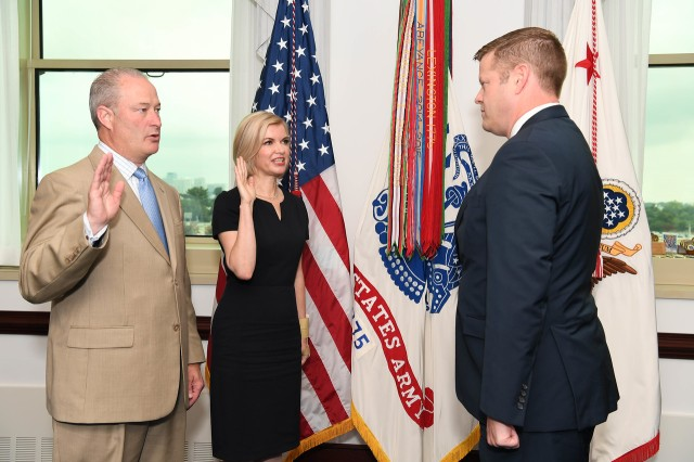Acting Secretary of the Army Ryan D. McCarthy, right, administers the CASA oath to Patrick Warren and Jill Castilla.