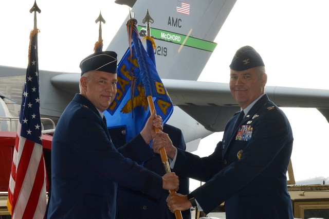 Maj. Gen. John Gordy II, commander of the U.S. Air Force Expeditionary Center, passes the colors to Col. Patrick O'Sullivan, Joint Base Lewis-McChord deputy garrison commander and commander of the 627th Air Base Group at an assumption of command ceremony Aug. 19 on McChord Field.