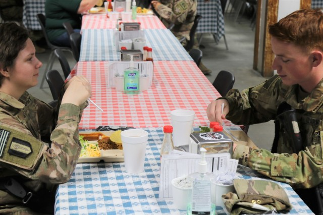 Spc. Kelsey Harty, a paralegal specialist with the 398th Support Battalion, 1st Infantry Division Sustainment Brigade, has lunch with her brother Spc. James Harty, a CH-47 Chinook helicopter repairer with the 2d Battalion, 501st Aviation Regiment, 1st Armored Division, at Bagram Air Field, Afghanistan, May 1, 2019. The brother and sister spent time together before James' promotion ceremony from the rank of specialist to sergeant. (U.S. Army photo by Sgt. Walter Carroll)
