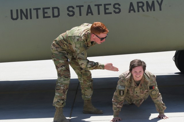Sgt. James Harty, a CH-47 Chinook helicopter repairer with the 2d Battalion, 501st Aviation Regiment, 1st Armored Division, playfully puts hit older sister Spc. Kelsey Harty, a paralegal specialist with the 398th Support Battalion, 1st Infantry Division Sustainment Brigade,in the push up position after his promotion ceremony to sergeant at Bagram Air Field, Afghanistan, May 1, 2019.  (U.S. Army photo by Sgt. Walter Carroll)