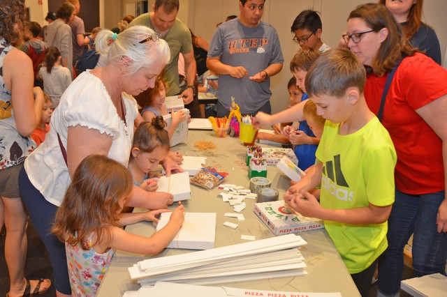 Children build homemade musical instruments during a session of this year's Summer Reading Program.