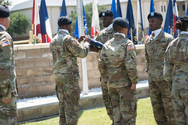 Before the retreat ceremony concludes, the color guard NCOIC inspects the flag ensuring it is to standard before the team marches off the field securing the flag.  Soldiers and leaders from Headquarters and Headquarters Company, 13th Expeditionary Sustainment Command, participated in a retreat ceremony on Hildner Field Friday. (U.S. Army photo by Sgt. 1st Class Kelvin Ringold)