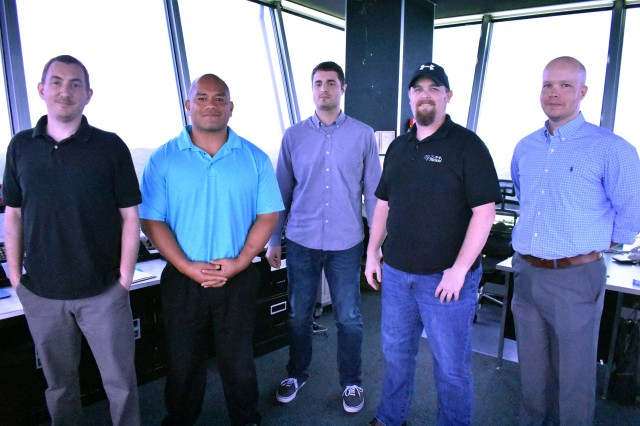"""From left, Norman Nichols, air traffic controller; Kekuakaninaualli """"Kekua"""" Aumua, supervisory air traffic control specialist; Adrien Smith, air traffic control specialist; Brian Greene, electronic technician; and Eric Anderson, supervisory air traffic controller, pose for a photograph inside the 102-foot air traffic control tower at Kastner Army Heliport at Camp Zama, Japan, Aug. 16. The team earned a 99-percent rating on their most recent inspection. Jeff Mays, an electronic technician who recently moved away, also contributed to the inspection."""
