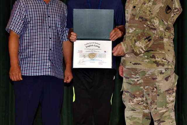 English Camp participant Gang, Dong-un receives a Certificate of Completion from USAG Daegu Garrison Chaplain Lt. Col. Alfred C. Grondski
