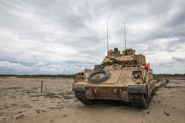 An Army M2 Bradley Fighting Vehicle stages out on a breaching range during a dry run of dismounted breach training conducted on a range in Poland, May 23, 2019. With funding from the Army's Manufacturing Technology Program, a team of scientists and engineers from the U.S. Army CCDC worked together to develop a cold spray process to repair costly turret gun mounts on the Army's M2 Bradley Fighting Vehicle.