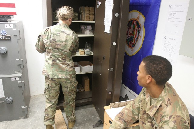 1st Lt. Bridget Auch, 247th Finance Management Support Detachment, removes currency from the vault to fill Spc. D'Are Perry's register at Camp Arifjan, Kuwait, Aug. 19, 2019. (U.S. Army National photo by Sgt. Ashley Breland)