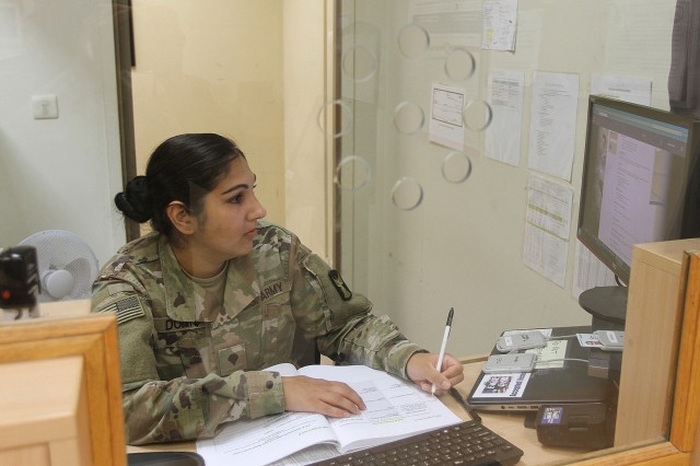 Between customers, Spc. Shaealanie Doane, 247th Finance Management Support Detachment, works on a self development program to improve her capabilities at Camp Arifjan, Kuwait, Aug. 19, 2019. (U.S. Army National photo by Sgt. Ashley Breland)