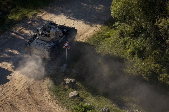 """A U.S. Army Bradley Fighting Vehicle with 1st Armored Brigade Combat Team, 1st Infantry Division, turns a corner enroute to a new location in """"the box"""" during the culminating force on force exercise of Combined Resolve XII at the Joint Multinational Readiness Center in Hohenfels, Germany Aug. 19, 2019. Combined Resolve is a biannual U.S. Army Europe and 7th Army Training Command-led exercise intended to evaluate and certify the readiness and interoperability of US forces mobilized to Europe in support of Atlantic Resolve.  (U.S. Army photo by Sgt. Thomas Mort)"""