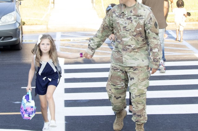 Staff Sgt. Levi Perez of Headquarters, Headquarters Battalion, walks his 7-year-old daughter Layla to her first day of school. Layla will be starting her first day of 2nd grade.