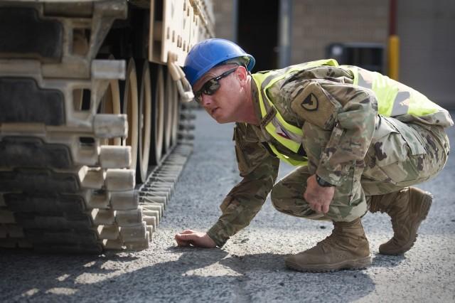 Sgt. 1st Class Matthew Zakrzewski, maintenance quality assurance, 401st Army Field Support Battalion-Kuwait inspects the tracks of a M2 Bradley Fighting Vehicle following repairs Aug. 15 at Army Prepositioned Stocks-5, Camp Arifjan, Kuwait.