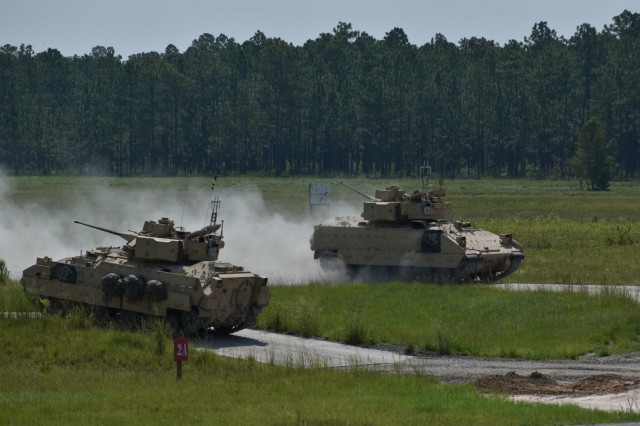 A Bradley Fighting Vehicle from B Co., 3rd Battalion, 15th Infantry Regiment, 2nd Armored Brigade Combat Team, passes another after completing a firing lane at Fort Stewart, Ga., Aug 14. Soldiers and crew evaluators conducted after-action reviews to assess tactics and battle strategy after each firing lane. (U.S. Army Photo by Spc. Jordyn Worshek, Released)