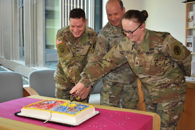 The Ansbach Health Clinic officially opened their new lactation room for breastfeeding moms during a ribbon cutting ceremony Aug. 22, 2019. Col. Steven Pierce (left), garrison commander, and Lt. Col. Daniel Cash (right), Ansbach Health Clinic commander, cut the cake with the help of Sgt. Rochelle Walsingham, a medic at the health clinic.