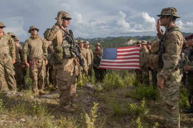 Spc. Eugene Bromberg (left with hand raised), an infantryman, is led in the oath of reenlistment by his commanding officer Army Cpt. Evan Dimakas (right with hand raised) in Poptun, Guatemala, July 15, 2019. The two are flanked by Soldiers from B Company, 182nd Infantry Regiment and Guatemalan Kaiblies. Bromberg, who immediately bonded with the Guatemalan special forces soldiers, asked that they be included in his reenlistment ceremony.