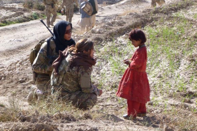 Wearing a black head cover, Army Chief Warrant Officer 4 Raquel Patrick, a member of Cultural Support Team-2, speaks with an Afghan child, Nov. 24, 2015. Female CST-2 members were deployed to Afghanistan with the primary duty of working with civilian women there.