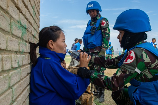 Indonesian air force members give water to a civilian role player during a training scenario for Khaan Quest 2019 at Five Hills Training Area in Ulaanbaatar, Mongolia, June 24, 2019.