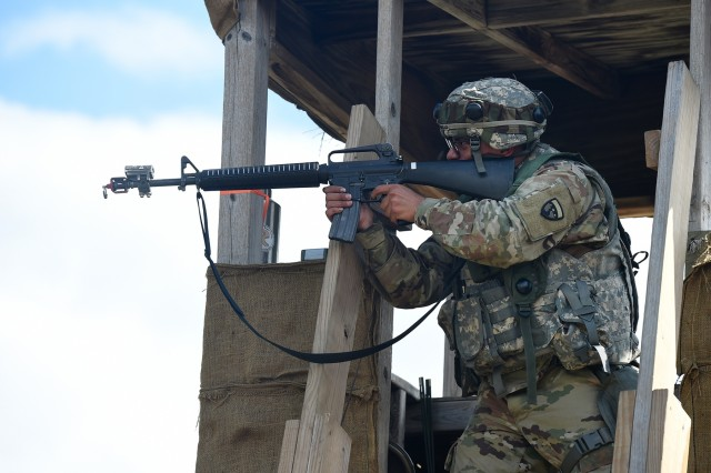 Spc. Dimitri Persad, Motor Transportation Operations Specialist, 211th Inland Cargo Transfer Company, Garden Grove, California, fires at the enemy from a guard tower during a day time attack on August 18, 2019. The opposition force attempted to infiltrate the southeast corner of the base prompting the quick reactionary force to respond to secure the area. Responding to a base attack is one of the scenarios evaluated by observer coach/trainers during the exercise. Army Reserve Soldiers traveled to Fort McCoy, Wisconsin to participate in the 86th Training Division's CSTX 86-19-04 during the month of August. Active duty and Army Reserve observer coach/trainers from First Army's 181 Multi-functional Training Brigade, 85th U.S. Army Support Command, 84th Training Command and 86th Training Division supported Army Reserve and National Guard Soldiers improve their functional and tactical skills by coaching and teaching them about tactical field craft in an austere environment. Soldiers were trained in objectives such as base defense operations, convoy operations and applying first aid on the battlefield. (U.S. Army Reserve photo by Sgt. David Lietz)