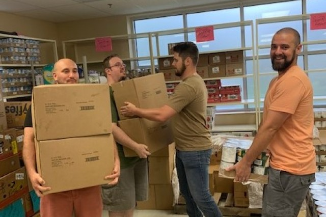 A team from the Army Contracting Command -- Aberdeen Proving Ground's Division C, carry boxes of food to be loaded in trucks for delivery as part of their community service at Harford County's Community Action Food Bank/Food Pantry.  The team included (left to right) contract specialists Jordan Good, Keven Strausser, Patrick Cruickshank, and Eric Pyles.