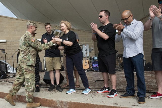 Fort Knox Garrison Commander Col. CJ King (left), presents the 2019 Commander's Cup to U.S. Army Human Resources Command at the start of MWR's Party in the Park Aug. 23, 2019.