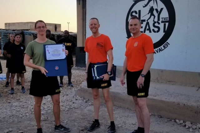Chief Warrant Officer 2 Melissa Huntley-Bosco, 529th Support Battalion, is awarded the Physical Readiness Training Badge and Certificate of Achievement for outstanding physical fitness performance by the 529th Support Battalion command team, Command Sgt. Maj. Brian Coleman and Lt. Col. Dennis Rohler, at Camp Taji, Iraq, Aug. 17, 2019. (U.S. Army National Guard photo by Sgt. 1st Class James Taylor)