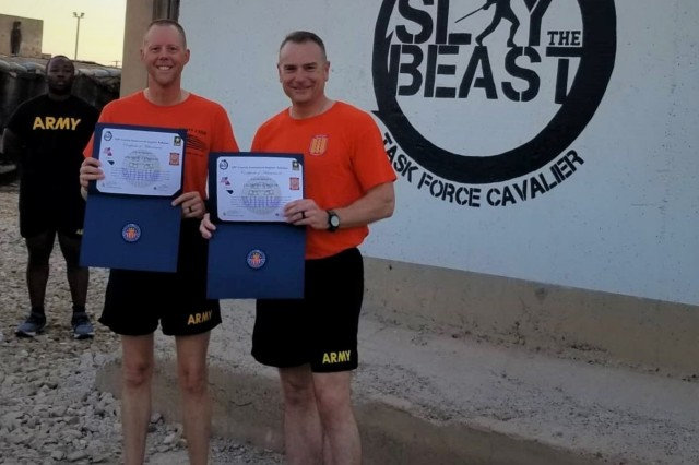 Command Sgt. Maj. Brian Coleman and Lt. Col. Dennis Rohler, the 529th Support Battalion command team, are awarded the Physical Readiness Training Badge and Certificate of Achievement for outstanding physical fitness performance while assigned to the 529th Support Battalion in support of Operation Inherent Resolve at Camp Taji, Iraq, Aug. 17, 2019. (U.S. Army National Guard photo by Sgt. 1st Class James Taylor)
