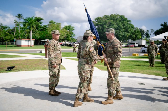 1st MSC Command Sgt. Maj. Robert Breck (right) passes the 1st MSC colors to Brig. Gen. Dustin A. Shultz, outgoing commander (center), during the change of command ceremony, Aug. 24, at the Soldier's Plaza in Fort Buchanan, PR.